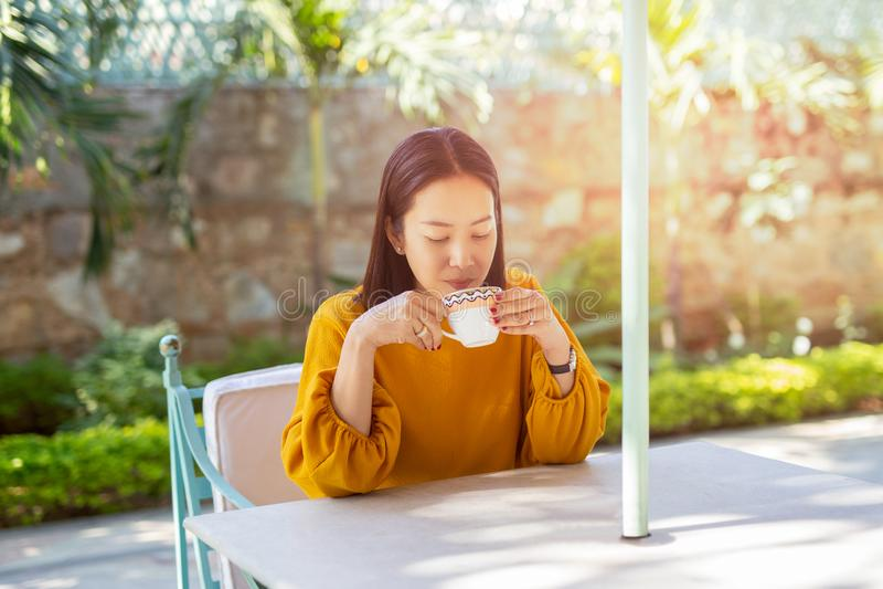 美女坐在咖啡馆的桌饮用的咖啡室外在庭院里 免版税图库摄影