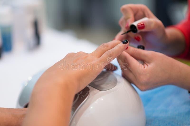 美女手特写镜头得到在温泉沙龙的修指甲 免版税图库摄影