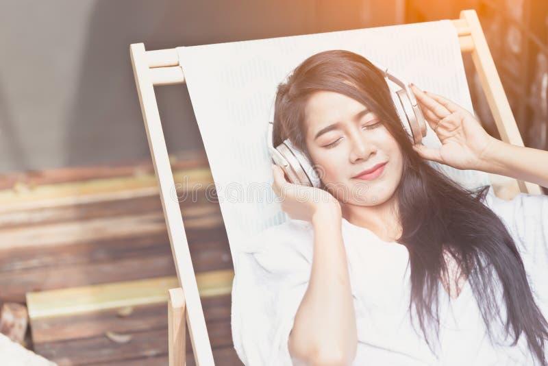 美女放松的水池边秀丽概念 愉快的女孩微笑anf听到与耳机的音乐 库存图片
