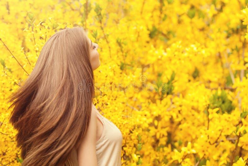 美女浪漫画象有长期吹的头发的在花卉背景 免版税库存图片