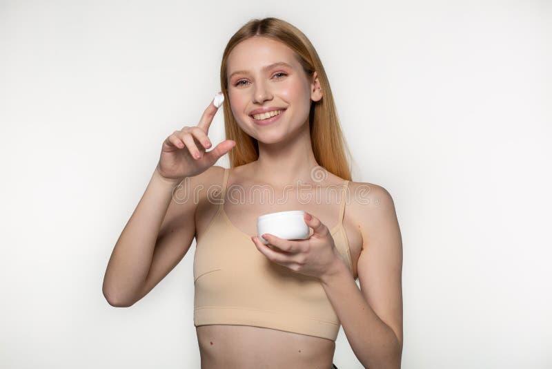 美女照片,关闭白色背景的演播室 与完善的秀丽女性面孔组成 拿着奶油 免版税库存图片