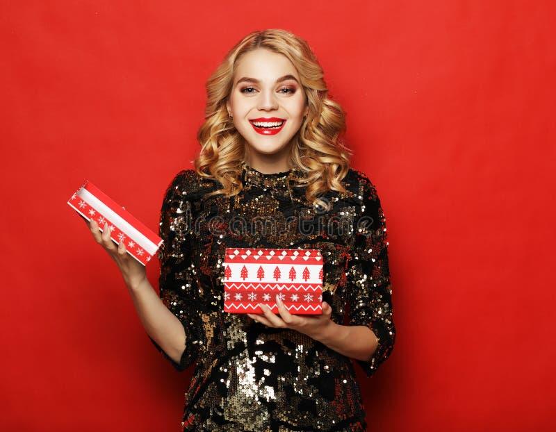 美女画象在晚礼服藏品打开了当前箱子被隔绝在红色背景 库存图片