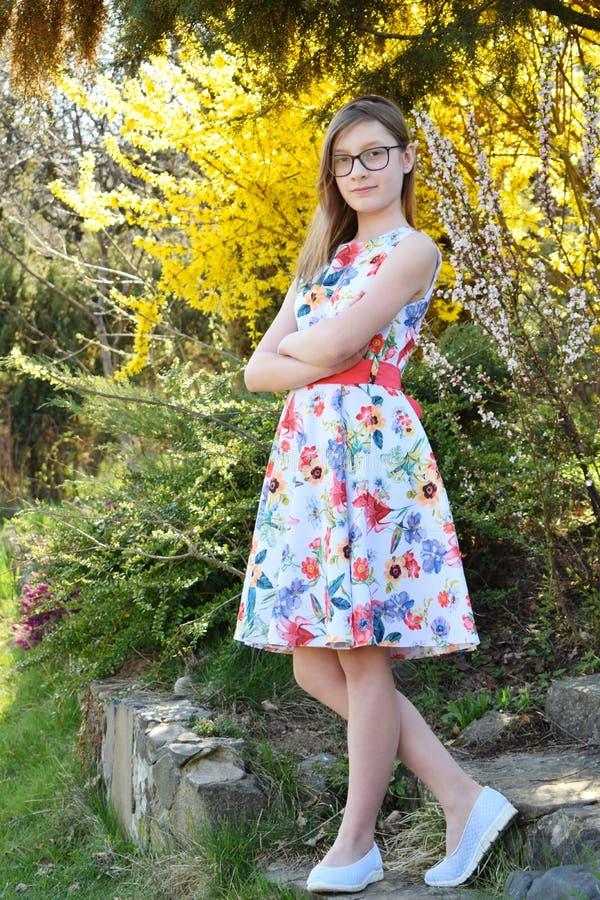 美女画象有玻璃和棕色头发的 年轻微笑的teneeger在休息在草中的绿色春天公园和 免版税库存照片