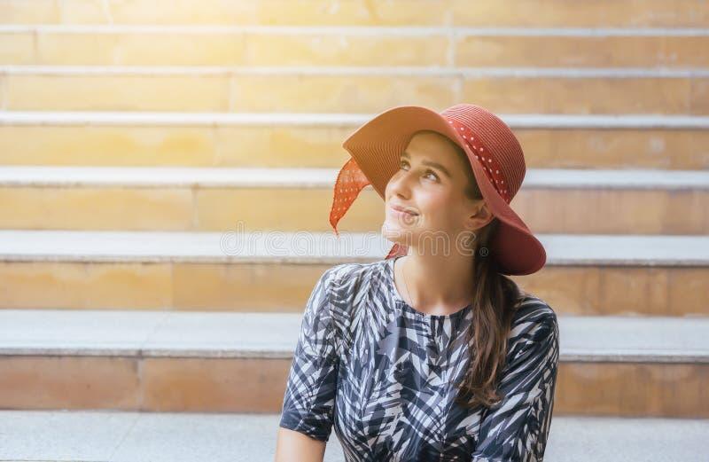 美女画象有红色帽子的坐在中心城市,愉快和微笑的情感的台阶,女性与正面attitu 库存图片