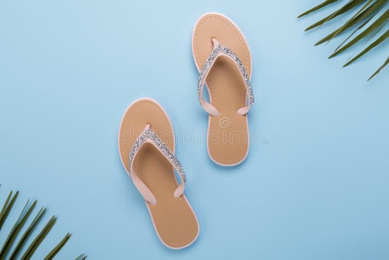 美女的在轻的淡色蓝色背景的海滩啪嗒啪嗒的响声 海滩夏天概念和假日概念,顶视图 免版税库存图片