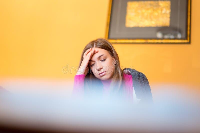 美女的开会在房子里,有头疼或担心,哀伤 免版税库存照片