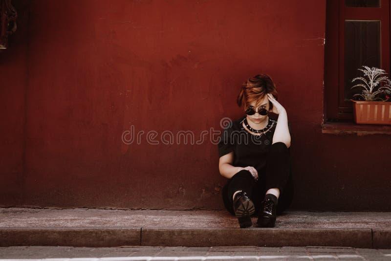 美女的画象坐在红色墙壁的地板 免版税库存图片