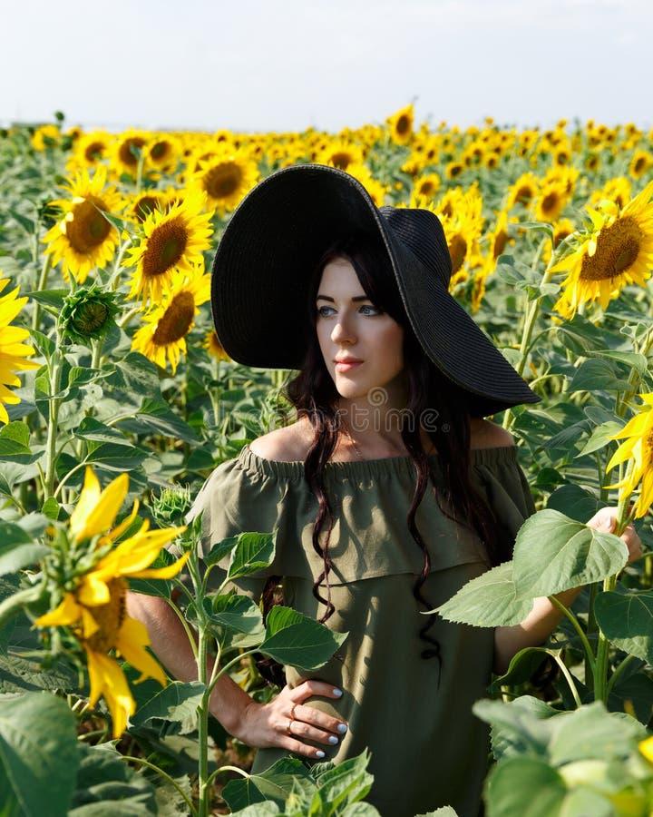 美女的画象有的向日葵 礼服和帽子的美丽的甜女孩走在向日葵的领域的,微笑 免版税库存图片