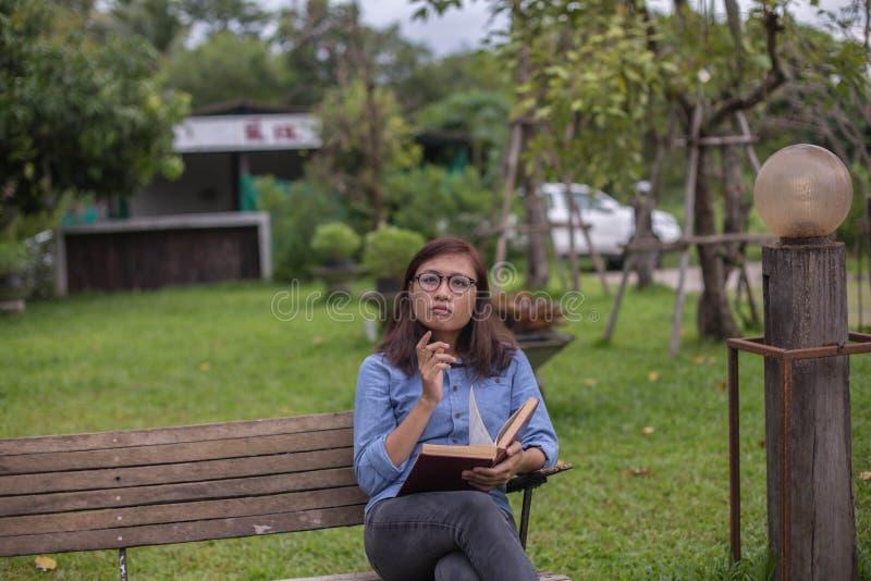 美女看书在庭院里 库存照片