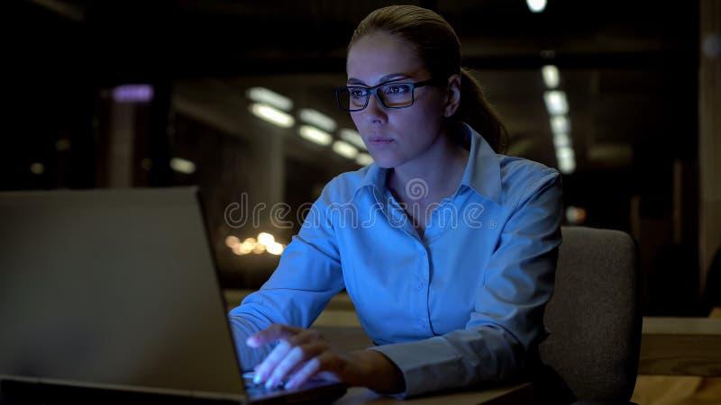 美女研究膝上型计算机的夜间在办公室,纯谨的雇员 免版税库存图片