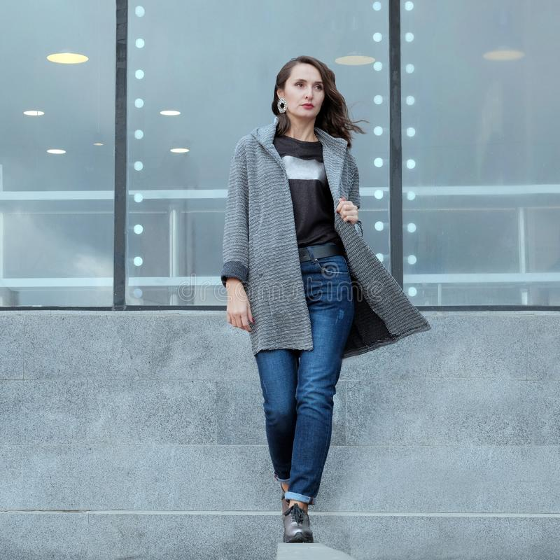 美女穿过城市走 外套和牛仔裤的时髦的浅黑肤色的男人继续 r 时尚广告demi 免版税库存照片