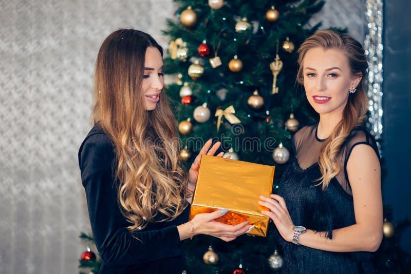 美女给一件礼物她的圣诞树的背景的朋友 库存照片
