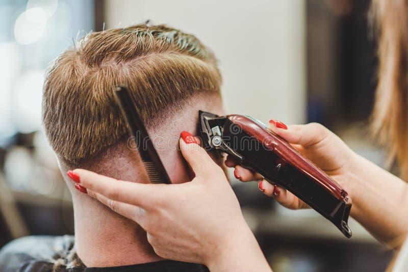 美女美发师切开沙龙的一个有胡子的人 库存图片