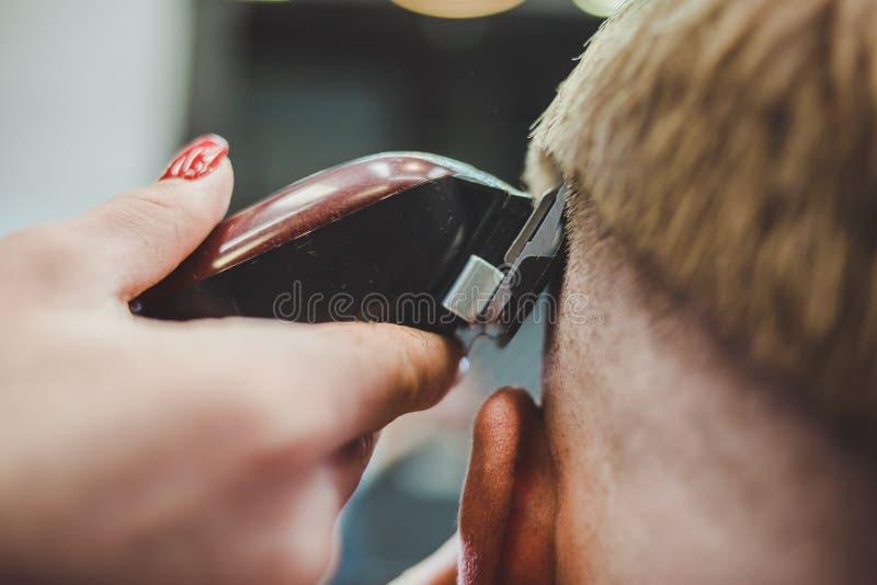 美女美发师切开沙龙的一个有胡子的人 免版税库存照片