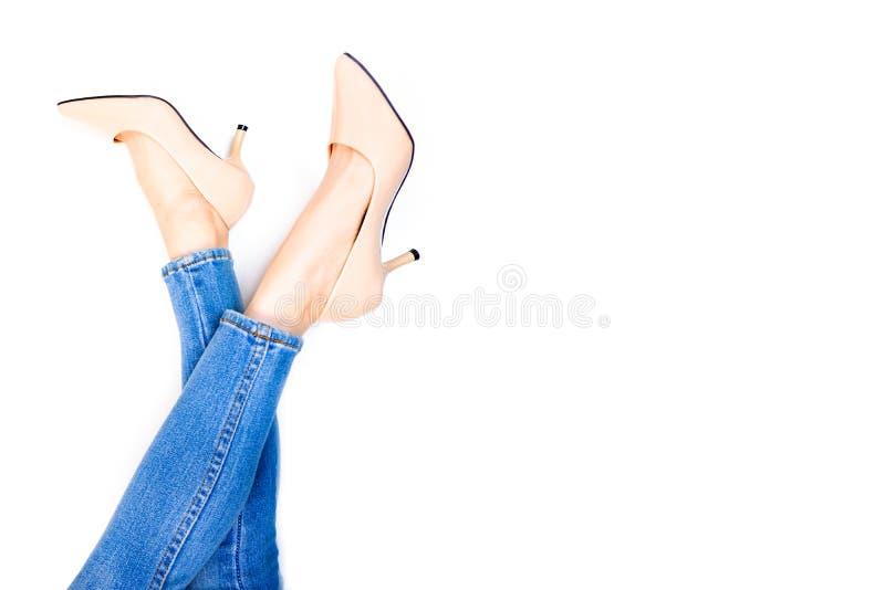 美女脚和亭亭玉立的腿在米黄中等高跟鞋 年轻女人腿画象  年轻女性佩带的牛仔裤蓝色 免版税库存照片