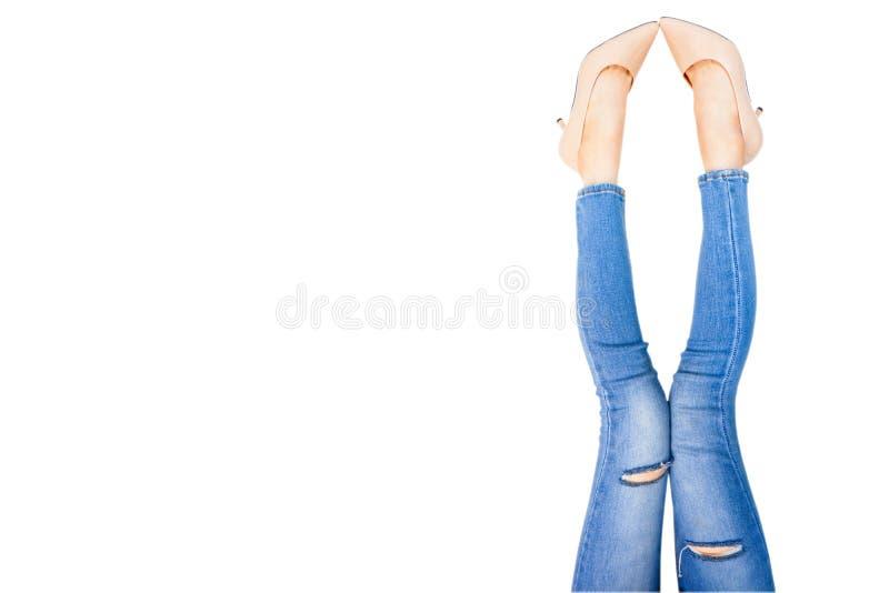 美女脚和亭亭玉立的腿在米黄中等高跟鞋 年轻女人腿画象  年轻女性佩带的牛仔裤蓝色 免版税库存图片