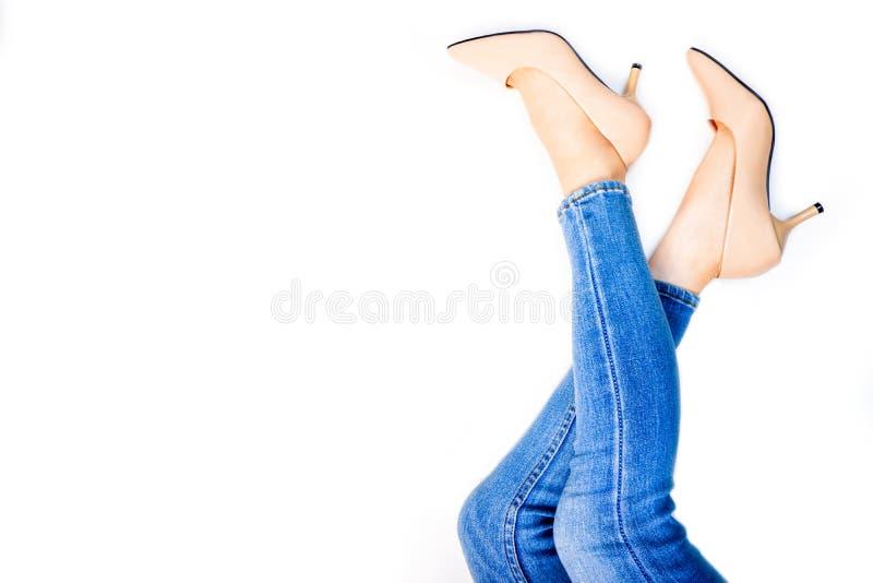 美女脚和亭亭玉立的腿在米黄中等高跟鞋 年轻女人腿画象  年轻女性佩带的牛仔裤蓝色 库存照片