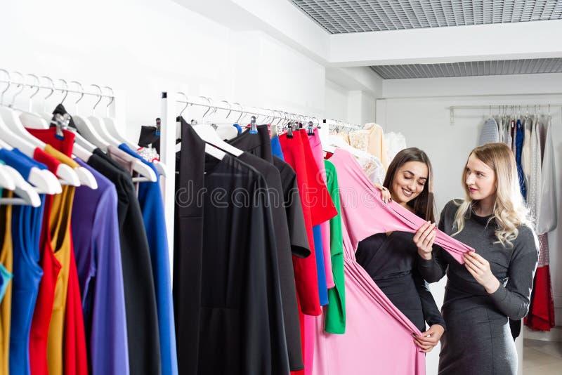 美女选择衣裳,谈话并且微笑着,当做在精品店时的购物 库存照片
