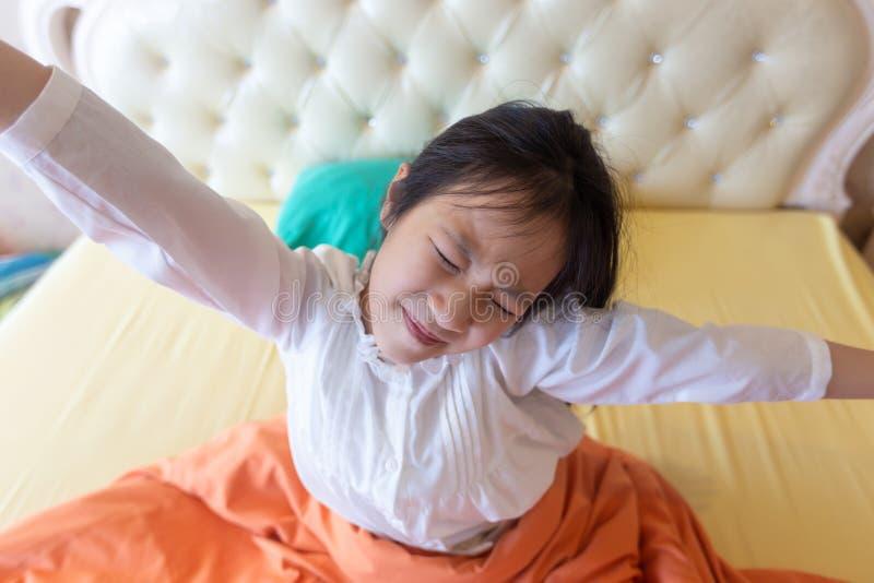 美女醒在她的床上的,舒展亚裔的女孩微笑和,健康,生活方式概念 免版税库存图片
