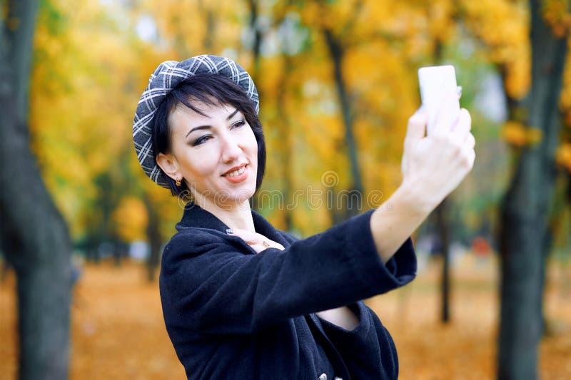 美女采取selfie由智能手机和获得乐趣在秋天城市公园,秋季,黄色叶子 免版税库存照片