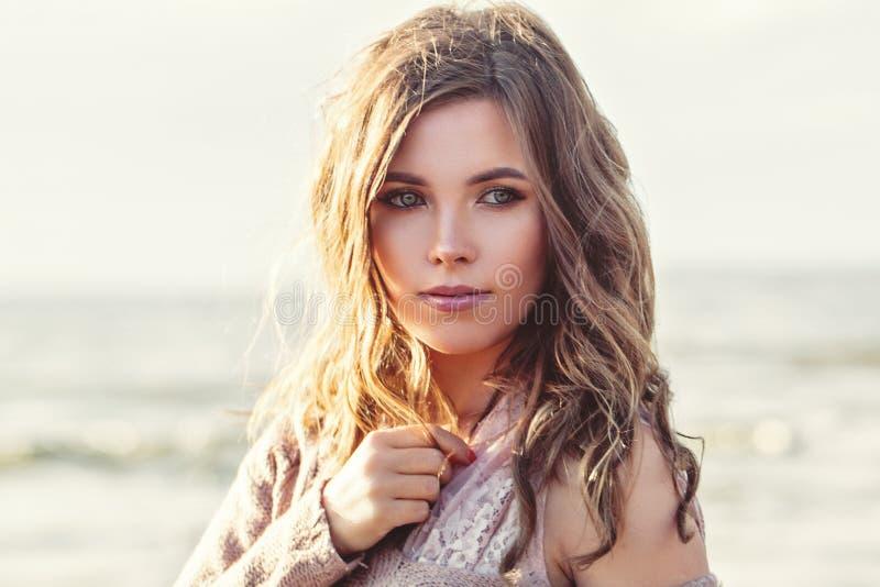 美女面孔特写镜头画象 有长的卷曲棕色头发的俏丽的女孩在海洋背景 完善的自然美人 免版税库存照片