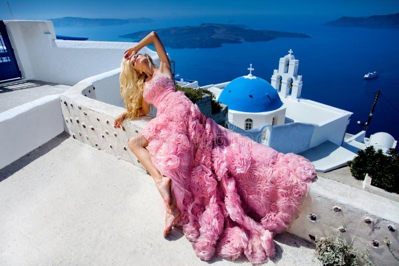 美女,一典雅的婚纱的新娘,站立以豪华圣托里尼海岛为背景 免版税库存照片