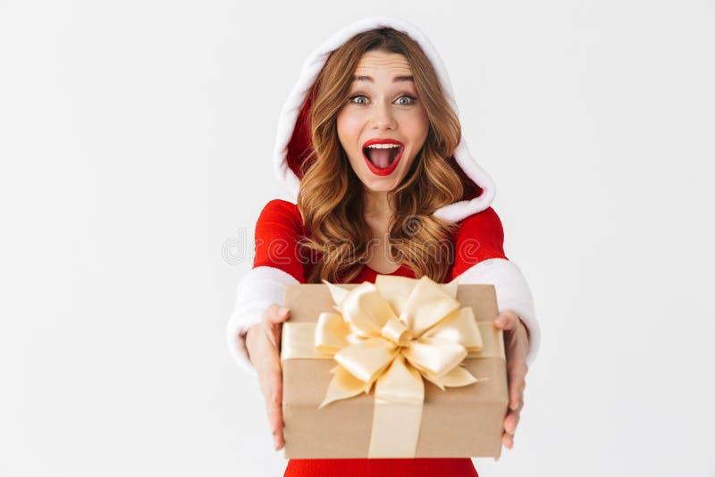 美女20s佩带的圣诞老人项目红色服装画象微笑和拿着当前箱子的,被隔绝在白色背景 库存照片