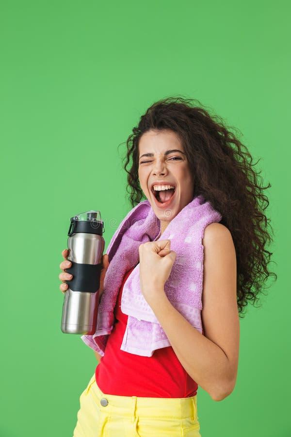 美女20s的图象运动服高兴的和饮用水的在训练以后 免版税库存照片