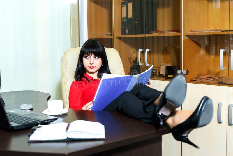 美好严肃妇女读文件在桌上 库存图片