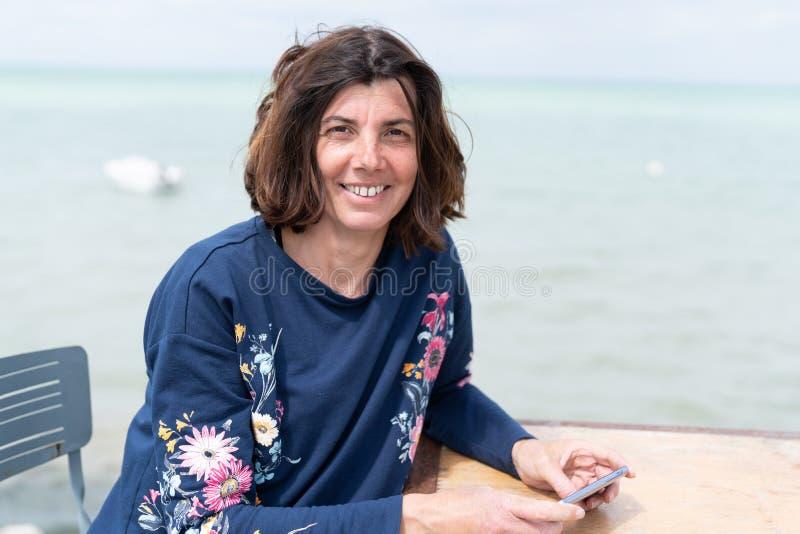 美好中间年迈的妇女微笑的笑在享受在桌海岸的海滩夏天 免版税库存照片