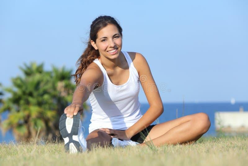 美好健身妇女舒展室外在草 免版税库存照片