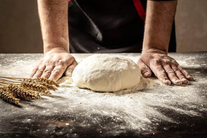 美好和坚强男人的手揉他们然后将做面包、面团或者比萨的面团 面粉蝇云彩  免版税库存图片