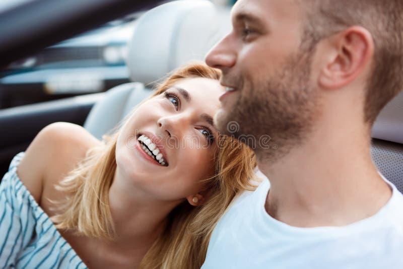 年轻美好夫妇微笑,坐在汽车在海附近 库存图片