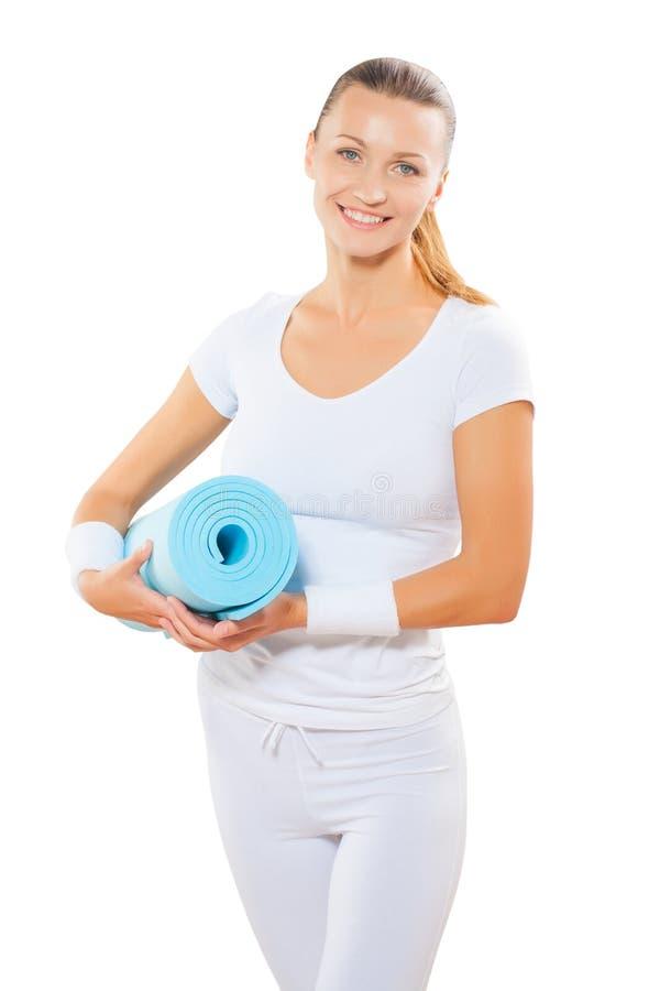 美好女性佩带炫耀衣裳holdin蓝色瑜伽的席子 库存图片