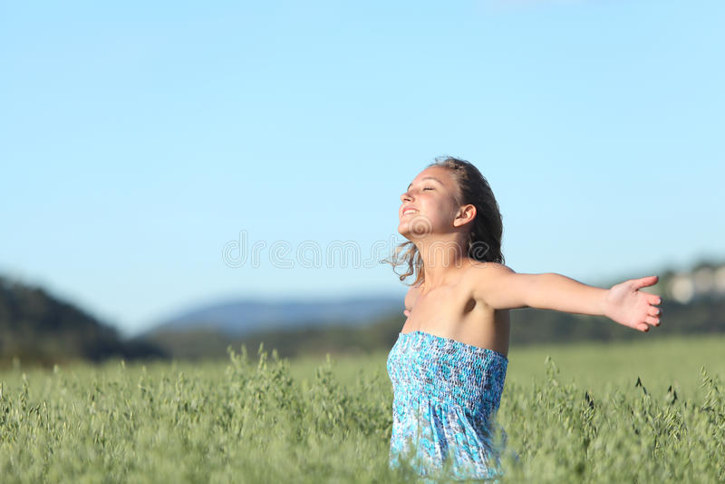 美好妇女呼吸满意对被举的胳膊在一个绿色燕麦草甸 图库摄影