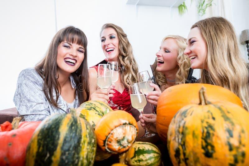 美好妇女摆在滑稽,当敬酒与她的朋友dur时 免版税库存图片