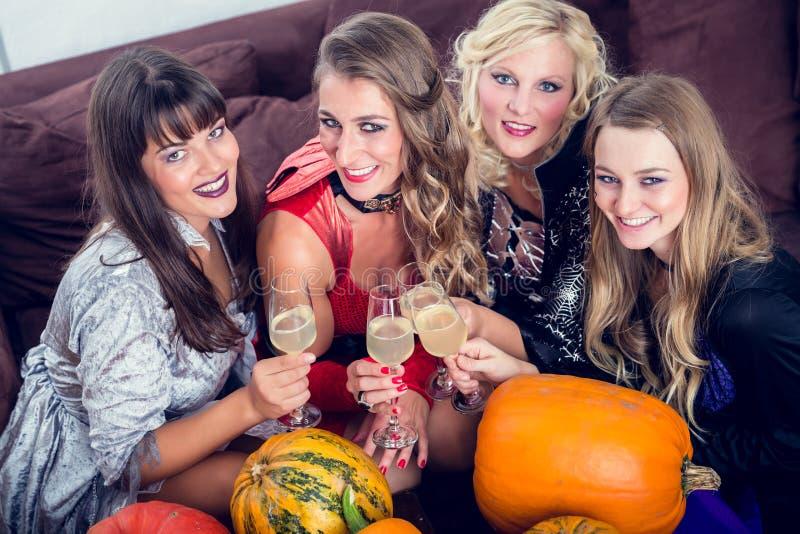 美好妇女摆在滑稽,当敬酒与她的朋友dur时 免版税库存照片