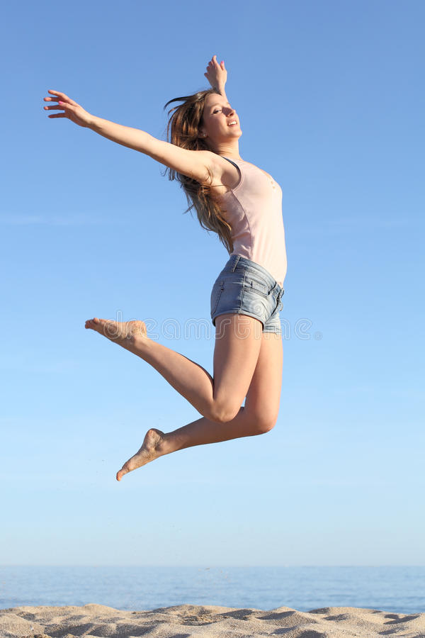 美好妇女跳跃愉快在海滩 免版税库存照片