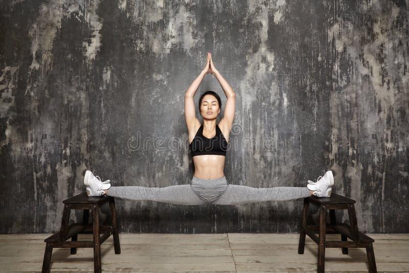 美好年轻亚洲妇女解决,做在运动服的普拉提锻炼 与瑜伽Asana的分裂,舒展 免版税库存照片