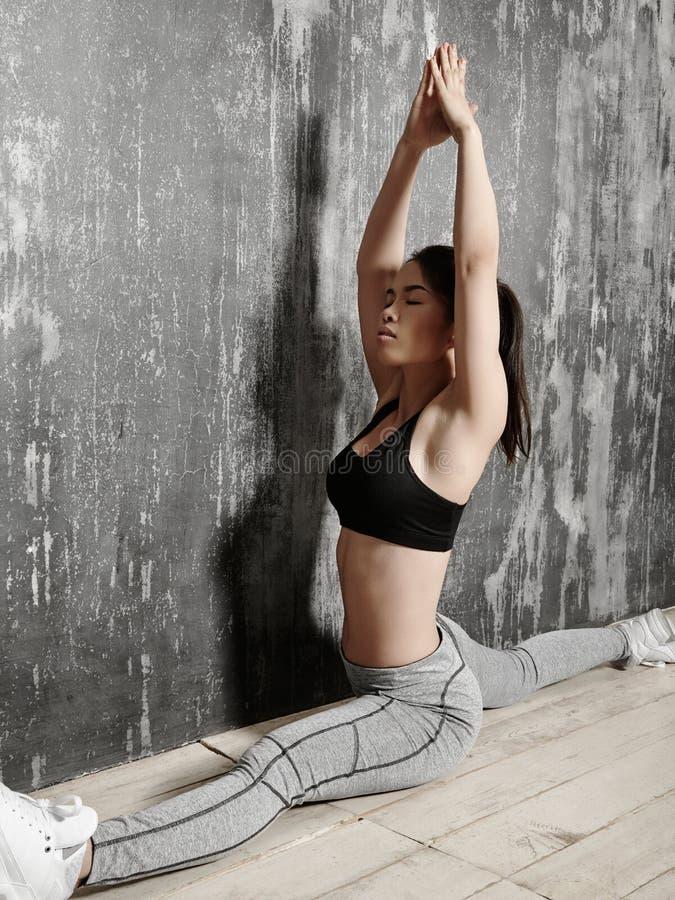 美好年轻亚洲妇女解决,做在运动服的普拉提锻炼 与瑜伽Asana的分裂,舒展 免版税图库摄影