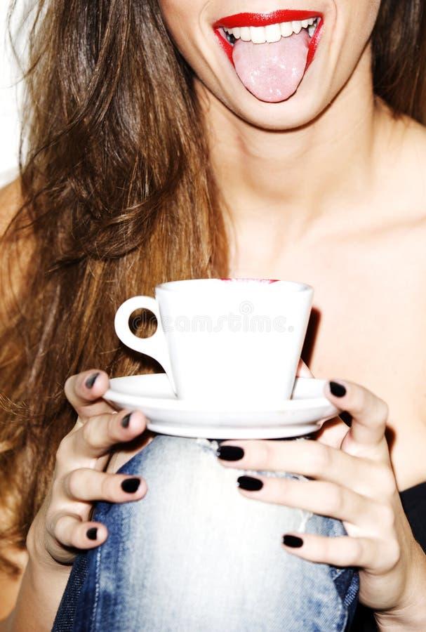 美好年轻女人微笑,舌头,拿着咖啡,艺术性的高钥匙 免版税库存照片