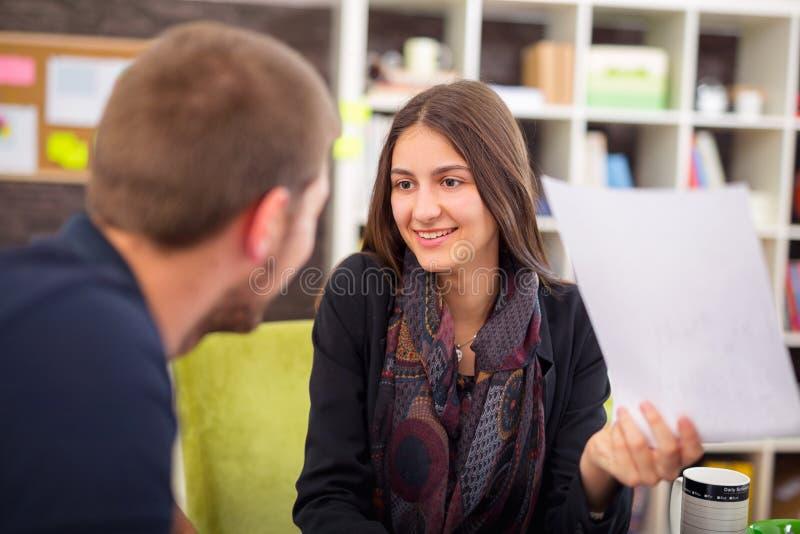 美好微笑的年轻女实业家坐的工作与一个年轻人在一个繁忙的办公室 库存图片