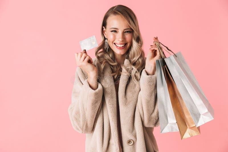 美好愉快激动年轻俏丽妇女摆在被隔绝在拿着购物带来和信用卡的桃红色墙壁背景 图库摄影