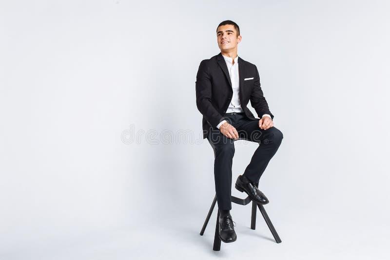 美好摆在的画象在演播室,白色背景,时髦的商人,时髦的人坐设计师椅子 免版税库存照片