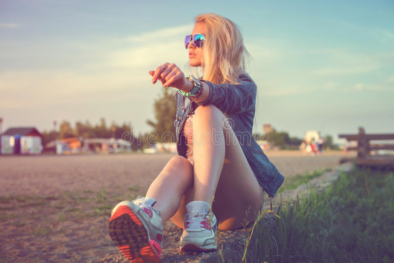 美好时尚少妇太阳镜坐 免版税库存照片