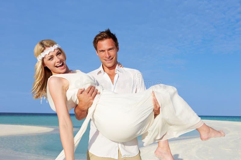 美好的海滩婚礼的新郎运载的新娘 图库摄影