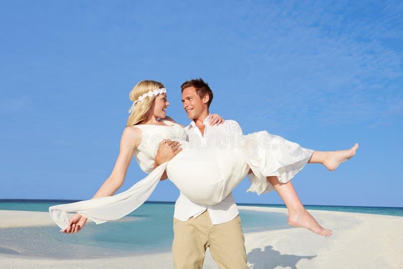 美好的海滩婚礼的新郎运载的新娘 免版税库存图片