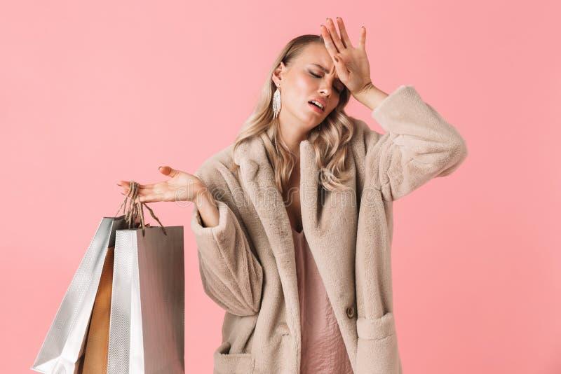 美好疲乏哀伤年轻俏丽妇女摆在被隔绝在拿着购物带来的桃红色墙壁背景 库存图片