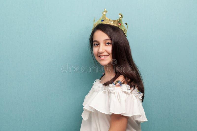 美好的一点公主穿戴侧视图画象在白色礼服和金黄王冠冠身分的,看照相机与 库存图片