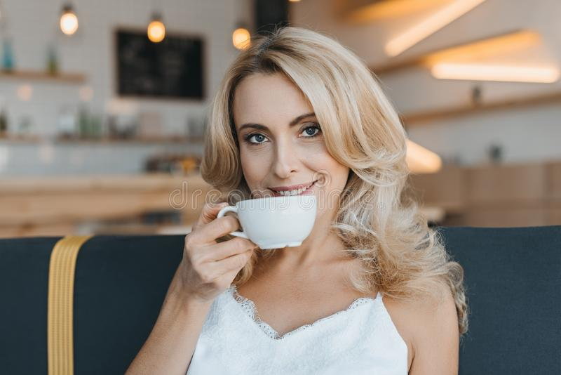美好的中部变老了妇女饮用的咖啡和微笑 图库摄影